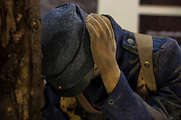 A soldier dressed in blue uniform in the trenches, wearing a blue soldier hat with a black brem, holding his hands up to his ears, for the gun noise in the war. Mannequin dressed as a soldier at a War Museum in Europe.