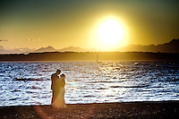 Amy and Todd stand alone on the beach at Golden Gardens park in Seattle, where they were married before the sun set over the Puget Sound. (Photo by Dan DeLong/Red Box Pictures)