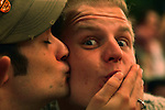 A guy plants a kiss on the cheek of his surprised friend during Oktoberfest in Munich, Germany. Oct. 2, 2007.