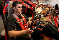 Fans (no model releases) try the racing simulators at the 2007 Speed Street festival. For several days leading up to the May races at the Lowe's Motor Speedway, uptown Charlotte streets are transformed into a showcase of motor sports and non-stop entertainment. ..Photo taken in 2007. Photographer also has images from 2008.