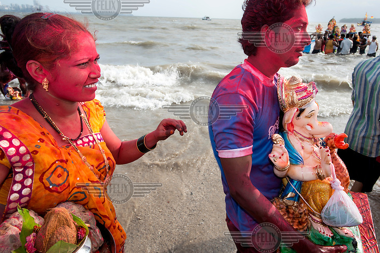 Families on Chowpatty beach, one of the many beaches in Mumbai where, at the end of the Ganesh Chaturthi festival, statues of Ganesh which have been displayed in homes thoughout the city are immersed in the sea. During the ten-day festival virtually every street in Mumbai erects a statue of Ganesh, the Hindu elephant deity. This has been the city's most popular celebration ever since the 1880s when it became a focus for India's struggle for independence and resistance against the British, who had banned all public assemblies.