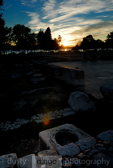 Sun setting over excavated Roman ruins, with lens-flare. Zadar, Croatia