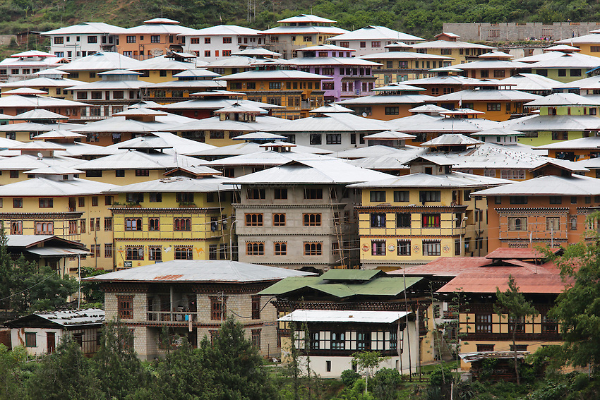 Modern town with traditional style contemporary architecture for a growing population, Punakha, Bhutan..Bhutan the country that prides itself on the development of 'Gross National Happiness' rather than GNP. This attitude pervades education, government, proclamations by royalty and politicians alike, and in the daily life of Bhutanese people. Strong adherence and respect for a royal family and Buddhism, mean the people generally follow what they are told and taught. There are of course contradictions between the modern and tradional world more often seen in urban rather than rural contexts. Phallic images of huge penises adorn the traditional homes, surrounded by animal spirits; Gross National Penis. Slow development, and fending off the modern world, television only introduced ten years ago, the lack of intrusive tourism, as tourists need to pay a daily minimum entry of $250, ecotourism for the rich, leaves a relatively unworldly populace, but with very high literacy, good health service and payments to peasants to not kill wild animals, or misuse forest, enables sustainable development and protects the country's natural heritage. Whilst various hydro-electric schemes, cash crops including apples, pull in import revenue, and Bhutan is helped with aid from the international community. Its population is only a meagre 700,000. Indian and Nepalese workers carry out the menial road and construction work.