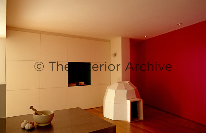 The focus of this low-ceilinged room is the red wall while the other wall comprises a series of flush cupboard units
