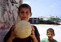 Old Gaza strip, bambino tiene in mano un pallone da calcio, un altro bambino osserva sullo sfondo