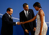 Pittsburgh, PA - September 24, 2009 -- United States President Barack Obama (C) and U.S. first lady Michelle Obama (R) welcome Italian Prime Minister Silvia Berlusconi to the welcoming dinner for G-20 leaders at the Phipps Conservatory on Thursday, September 24, 2009 in Pittsburgh, Pennsylvania. Heads of state from the world's leading economic powers arrived today for the two-day G-20 summit held at the David L. Lawrence Convention Center aimed at promoting economic growth. .Credit: Win McNamee / Pool via CNP