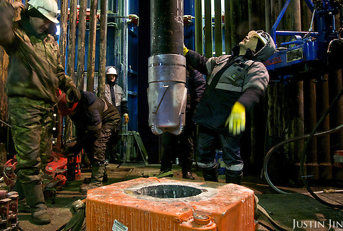 Workers prepares to drill into the permafrost at a well in Novy Urengoi, Siberia, Russia. The drill bit, embedded with diamond discs along the cutter, costs around 50,000 euros each. It is pushed down by a 10-ton load and turns at up to 200 revs per minute. <br /> <br /> Russia has some of the world's largest natural gas deposits.