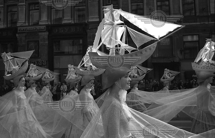 Woman with model ships on their heads march in a naval parade in St Petersburg.