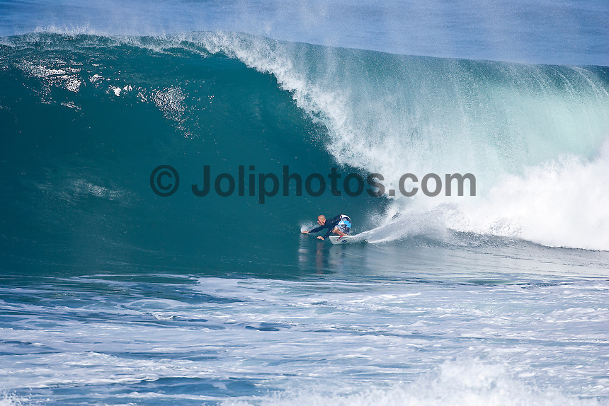 HALEIWA, HI (Sunday Dec. 6, 2009) Kelly Slater (USA) surfing ten to fifteen feet surf rolling into Backdoor and Pipeline on the North Shore on the 40th Anniversary of the biggest surf ever to hit the Hawaiian Islands. ..The northern hemisphere winter months on the North Shore signal a concentration of surfing activity with some of the best surfers in the world taking advantage of swells originating in the stormy Northern Pacific. Notable North Shore spots include Waimea Bay, Off The Wall, Backdoor, Log Cabins, Rockpiles and Sunset Beach... Ehukai Beach is more  commonly known as Pipeline and is the most notable surfing spot on the North Shore. It is considered a prime spot for competitions due to its close proximity to the beach, giving spectators, judges, and photographers a great view...The North Shore is considered to be one the surfing world's must see locations and every December hosts three competitions, which make up the Triple Crown of Surfing. The three men's competitions are the Reef Hawaiian Pro at Haleiwa, the O'Neill World Cup of Surfing at Sunset Beach, and the Billabong Pipeline Masters. The three women's competitions are the Reef Hawaiian Pro at Haleiwa, the Gidget Pro at Sunset Beach, and the Billabong Pro on the neighboring island of Maui...Photo: Joliphotos.com