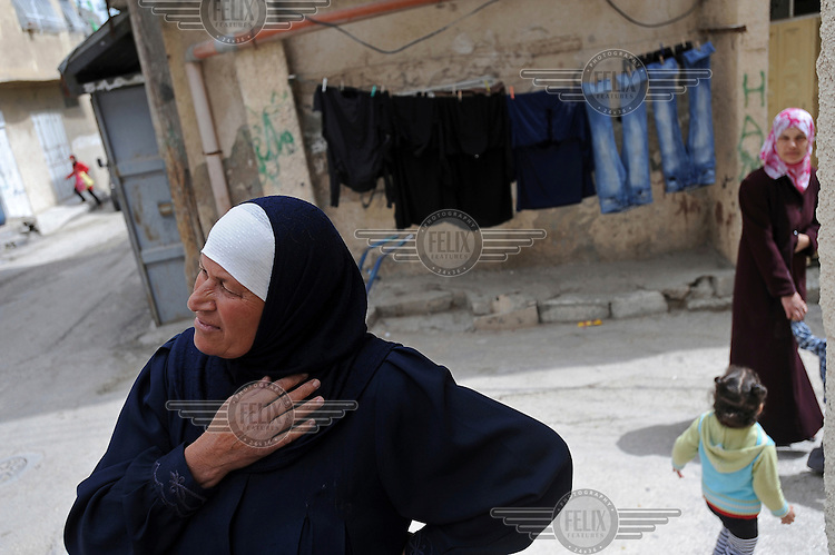 Um Hazem, a 56-year-old woman originally from Lod in central Israel, stands in a street in the Palestinian refugee camp of Al-Amari, near Ramallah.