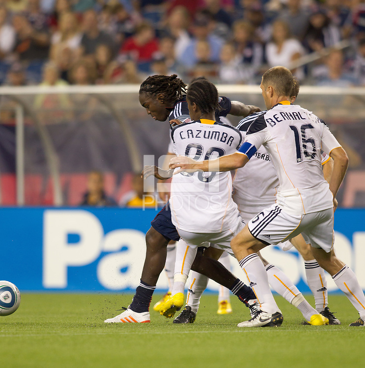 New England Revolution midfielder Shalrie Joseph (21) dribbles in a crowd. The New England Revolution defeated LA Galaxy, 2-0, at Gillette Stadium on July 10, 2010.