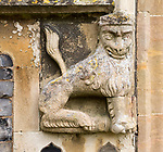 Figure of a crowned lion carved in stone on the entrance doorway to the church, Peasenhall, Suffolk, England, UK. One of a pair this one has its tail intact.