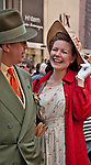 Woman in a vintage dress, red coat, and a large straw hat in the Easter Parade on Fifth Avenue in New York City