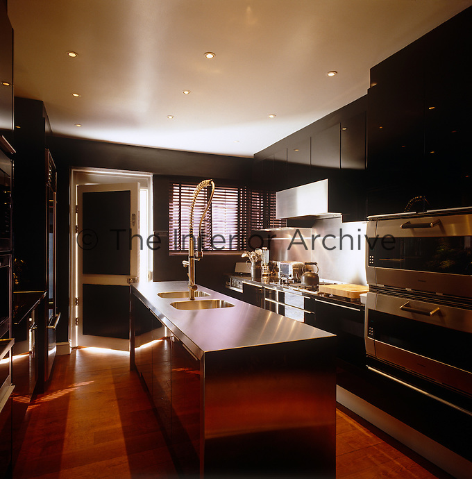 A long central kitchen island with a double sink dominates this contemporary black and stainless steel kitchen