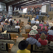 Cowboy Church. Texas, USA. 2007. Sunday service at the 1,000 Hills Cowboy Church. The congregation sit in casual attire at the church, they wear their hats and boots and in attitude is relaxed. They are entertained by the Cowboy Church band before the sermon is held by Pastor Ron Moore.