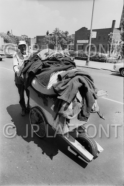 Brooklyn, New York City, NY. August, 1971. <br /> A man carrying a heap of clothes on a cart. Poor housing, poverty, unemployment and crime did not facilitate the poor inhabitants during the heatwave.
