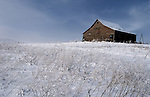 Snow and small brush surrounds an aging wooden farmhouse in the Palouse as seen in the winter.