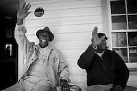 Sol Legare residents Ernest Parks and James Brown wave to passers-by from the front porch of the recently restored Seashore Farmers' Lodge on James Island. Sol Legare is  a Gullah community, most of whom can trace their families  back as many as seven generations to the original settlers who were freed slaves.