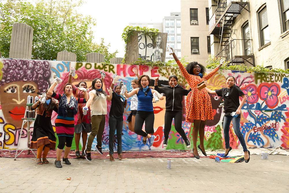 A group of the excited participants jumping for joy in front of their mural.