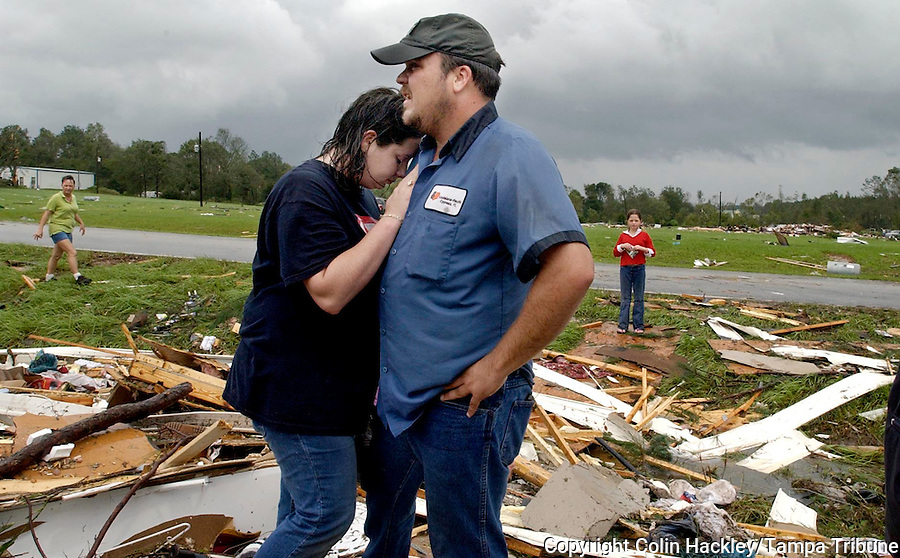 BLOUNTSTOWN, FL. 9/16/04-Santana Sullivan leans against her fiancee Chris Ammons as they look at the remains of their mobile home Thursday near Blountstown. The couple heeded the warnings of relatives and left their home before the tornado struck. They are to be married in two weeks. COLIN HACKLEY PHOTO