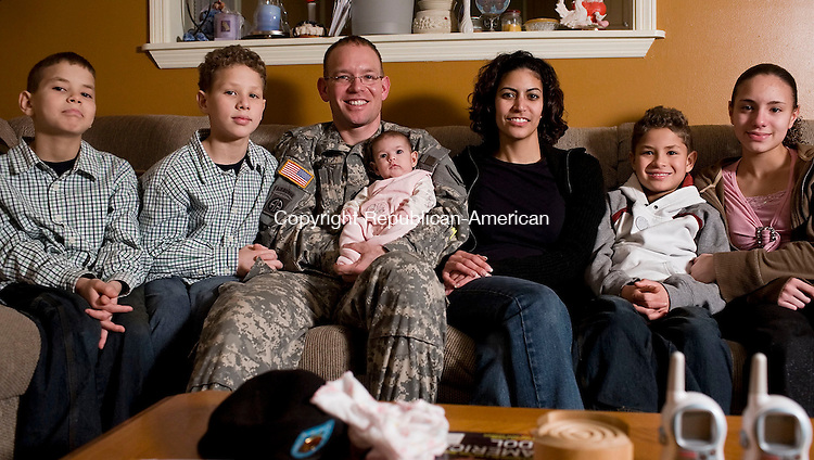 WATERBURY--12 January 07--011208TJ16 - Staff Sgt. John Sanchez, third from left, holds 2-month-old Marisela while sitting with his family, from left, Michael, 10, John Nicholas, 11, his wife, Raquel, Joseph, 8, and Latisha, 13, at their Waterbury home on Saturday, January 12, 2008. (T.J. Kirkpatrick/Republican-American)