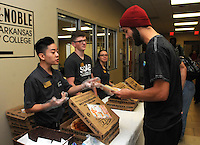 NWA Democrat-Gazette/FLIP PUTTHOFF <br /> Fuxing Do (cq) (left) with the NWACC Student Ambassador and Activities Board serves pizza at the meet and greet event for students and Evelyn Jorgenson, college president.