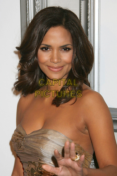 HALLE BERRY .Hosts the ESSENCE Black Women in Hollywood Luncheon held at The Beverly Hills Hotel, Beverly Hills, CA, USA, 19th February 2009..half length strapless gold silver patterned print metallic dress hair down hand waving ring  .CAP/ADM/KB.©Kevan Brooks/Admedia/Capital PIctures