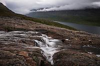 Mountain river flows above lake Teusjaure, Kungsleden trail, Lapland, Sweden