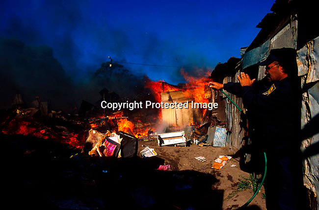 DIENVFI00063.Enviroment. Fire. An unidentified policeman is trying to put out a raging  shackfire on July 6, 2001, in Duncan Village, a poor township outside East London in Eastern Cape province, South Africa. Eastern Cape is the poorest province in South Africa. Shack fires are very common as the shacks are built very close to each other and people are using paraffin stoves which easily fall over and the fires spread quickly. South Africa is facing a severe backlog of housing for the poor. The ANC government promised to build 1 million houses during the first democratic election in 1994..©Per-Anders Pettersson/iAfrika Photos