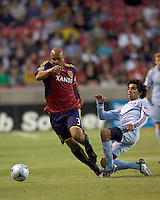 Real Salt Lake midfielder/defender Robbie Russell (3) dribbles through tackle by Colorado Rapids midfielder Mehdi Ballouchy (8). Real Salt Lake tied the Colorado Rockies, 1-1, at Rio Tinto Stadium on June 6, 2009.