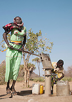 Girls of the Nuba tribe pumping water from a well in the village of Nyaro, Kordofan region, Sudan