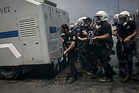 n this Tusday, Jun. 11, 2013 photo, anti-riot policemen take cover behind a water canyon truck as they charge against protesters during clashes at the streets of Taksim Square in Istanbul, Turkey. (Photo/Narciso Contreras).