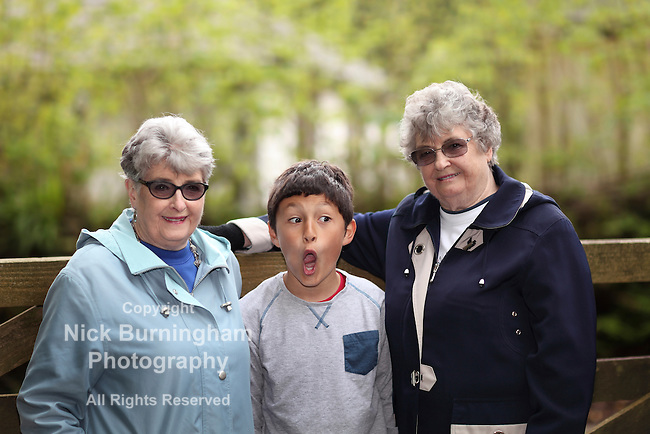 Multi-racial grandson with elderly twin sisters - shallow depth of field