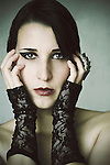Close-up portrait of a young woman with pale skin and shiny silver eyes staring at the camera, with her head resting on her hands with lace gloves and a silver ring.