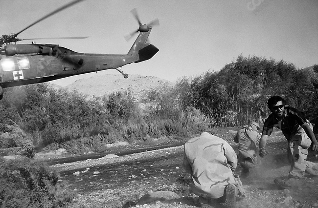 A US medivac helicopter takes away two wounded Afghan civilians who were caught in crossfire in a battle between US forces and Taliban, Gonbaz village, Kandahar Province, October 2005.