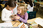 Education Elementary Public Grade 2 two female students observing and examining birds' nests horiozntal
