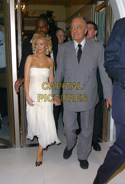 "CHRISTINA AGUILERA & MOHAMMED AL FAYED.Open Harrods Summer Sale, knightsbridge, London,.28th June 2004..full length bleach blonde curly hair strapless white floaty beaded embroidered dress black stilettoes holding hands silver letter ""A"" pendant necklace heavy make up.sales@capitalpictures.com.www.capitalpictures.com.©Capital Pictures"