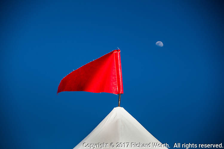 A festive red pennant on top of a vendor display tent with a waxing gibbous moon in a clear blue sky.