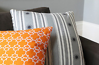 Detail of two cushions, one covered in an orange geometric pattern, the other in stripes of pale grey with rows of dark grey stars