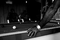 Sunday afternoon leisure time in the bar playing snooker at Agua Branca gold mining village, Para State, Amazon, Brazil. Luxury and ostentation, prospector wears a gold watch.