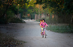 Wichi indigenous girls ride a bike in an indigenous neighborhood of Embarcacion, Argentina. The Wichi in this area, largely traditional hunters and gatherers, have struggled for decades to recover land that has been systematically stolen from them by cattleraisers and large agricultural plantations.