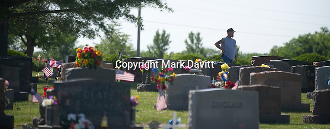 Randy Eaton of Indianola surveys the decorated grave sites on Memorial Day.