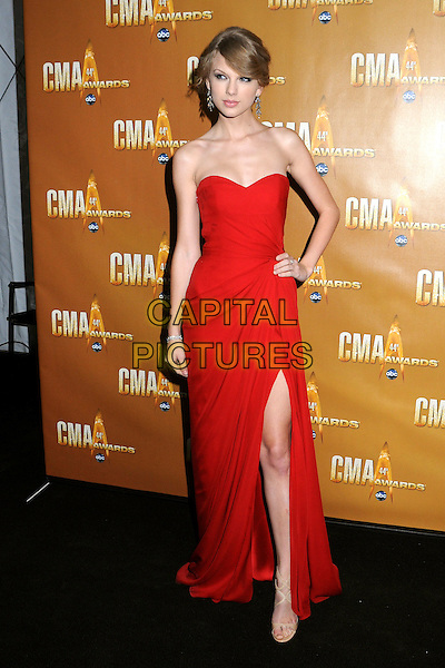 TAYLOR SWIFT .44th Annual CMA Awards, Country Music's Biggest Night, held at Bridgestone Arena, Nashville, Tennessee, USA, 10th November 2010..CMAs country music full length red dress slit split long maxi hand on hip  strapless .CAP/ADM/LF.©Laura Farr/AdMedia/Capital Pictures.