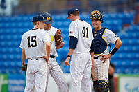 Michigan Wolverines pitching coach Chris Fetter (41) talks with relief pitcher Jack Bredeson (34) as third baseman Jimmy Kerr (15) and catcher Harrison Salter (11) look on during a game against Army West Point on February 18, 2018 at Tradition Field in St. Lucie, Florida.  Michigan defeated Army 7-3.  (Mike Janes/Four Seam Images)