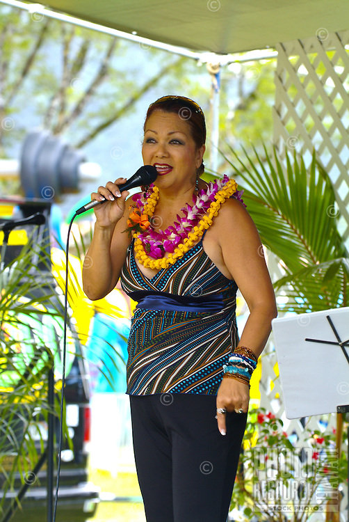 Local Hawaiian entertainer and singer Melveen Leed, wearing two flower lei, performing at Windward Community College ho'olaulea festival in the community of Kaneohe, Oahu. Melveen often sings about Hawaiian cowboys -- paniolos. One of her famous son