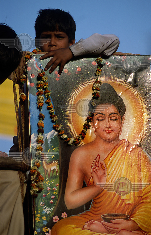 A young boy, formerly a dalit (untouchable) now a convert to Buddhism, with image of the Buddha and a marigold garland.