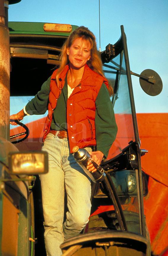Female farmer on tractor.