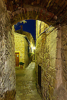 Narrow walkway through arched opening at night, Pienza, Italy, Tuscany