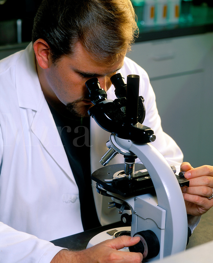 Lab tech looking in a microscope