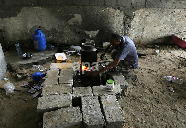 "A Palestinian man cooks on firewood in a destroyed house in Khan Yunis in the southern Gaza Strip on September 11, 2014. Israel's deputy foreign minister,Tzahi Hanegbi , warned that Hamas was likely to resume ""violence"" if it feels it has made no political gains from upcoming talks in Cairo. Photo by Abed Rahim Khatib"